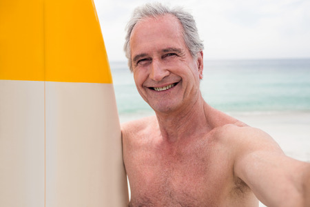 escapism: Portrait of happy senior man standing on beach with surfboard on a sunny day
