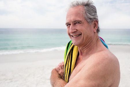 escapism: Portrait of happy senior man standing on beach with towel on shoulder Stock Photo