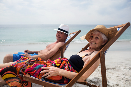 Happy senior couple relaxing on deckchairs at beach on a sunny day Stock Photo