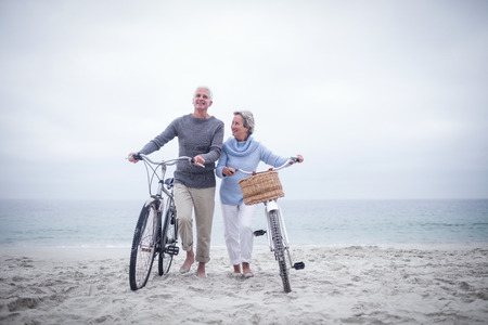 Senior couple having ride with their bike on the beach Foto de archivo