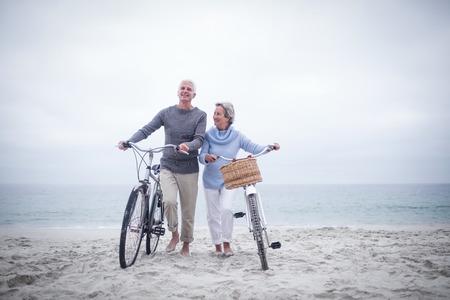 Starszy para z ich jazdę rowerem na plaży Zdjęcie Seryjne