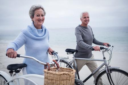 happy seniors: Happy senior couple having ride with their bike on the beach