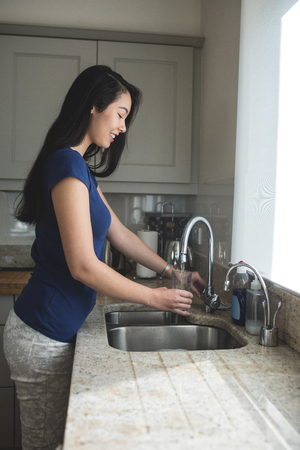 Young woman washing a glass in kitchen sink at home