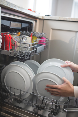 arranging: Woman in kitchen arranging plates in dish washer