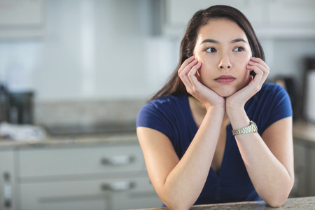 daydreaming: Young woman daydreaming in kitchen at home