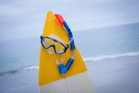 scuba mask: Close-up of surfboard with scuba mask on the beach Stock Photo