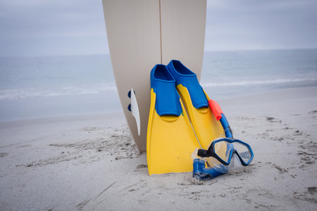 scuba mask: Surfboard with flippers and scuba mask on the beach Stock Photo