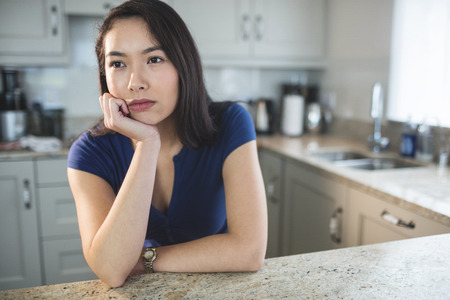 Young woman daydreaming in kitchen at home
