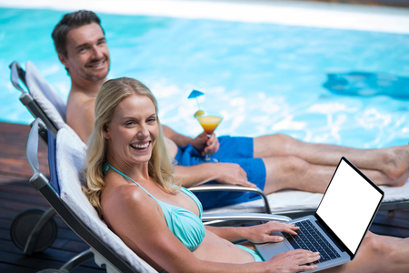 Happy couple sitting near pool with a laptop and martini glass Reklamní fotografie