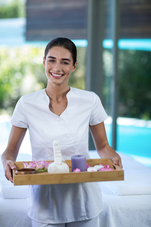 Portrait of female masseur holding a tray with spa therapy products Stock Photo