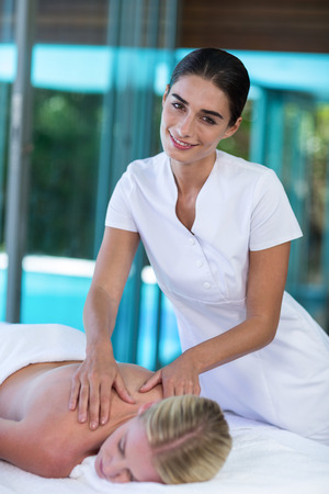Woman receiving back massage from masseur in spa