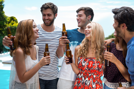 near beer: Group of happy friend holding beer bottles near pool