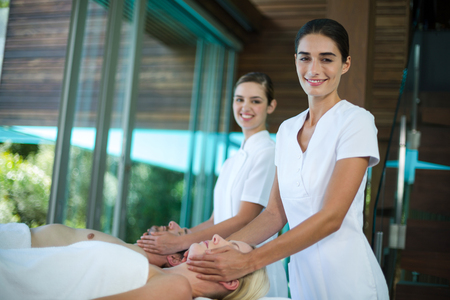 face massage: Couple receiving a face massage from masseur in spa Stock Photo
