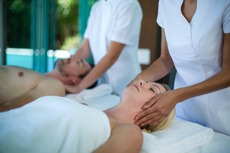 face massage: Woman receiving a face massage from masseur in spa