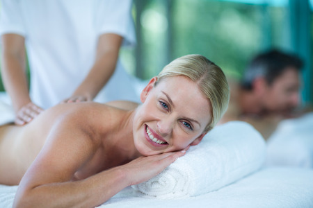 Portrait of woman receiving back massage from masseur in spa Stock Photo