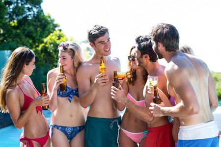 near beer: Group of happy friend holding beer bottles near pool