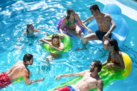 fun day: Group of friends having fun in swimming pool on a sunny day Stock Photo