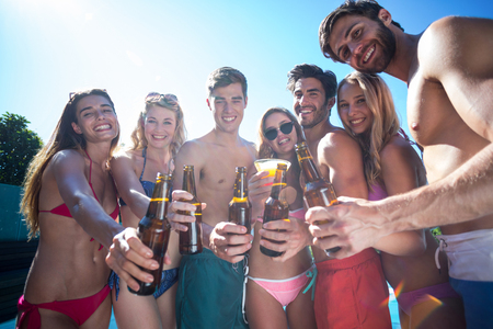 near beer: Group of happy friends showing beer bottles near the pool on a sunny day