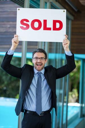 real estate sold: Excited real estate agent holding sold sign at resort
