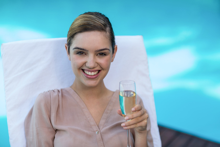 champagne flute: Businesswoman relaxing on sunlounger and holding champagne flute near pool Stock Photo