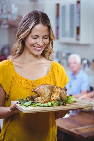 thanksgiving adult: Smiling woman holding cutting board with meat at home