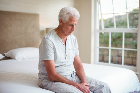 man looking down: Worried senior man looking down while sitting on bed in room Stock Photo