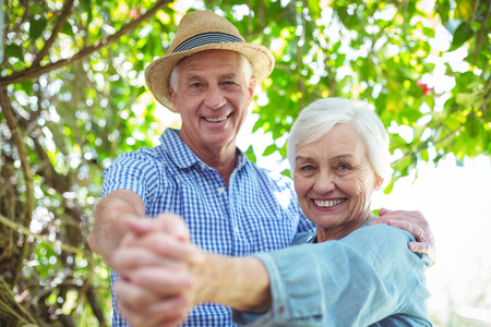 Portrait of cheerful retired couple dancing outdoors