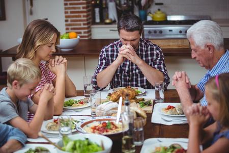 family praying: familia multi generación de rezar con los abuelos sentados en la mesa de comedor en el hogar