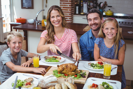 Portrait of smiling family sitting at dining table