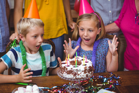 siblings: Shocked siblings with birthday cake at home Stock Photo