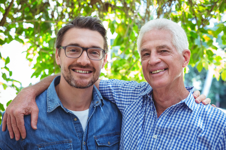 arm around: Portrait of happy father and son with arm around while standing outdoors Stock Photo
