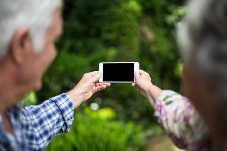 Senior couple taking selfie through smart phone in back yard