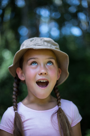 back yard: Surprised girl looking up in back yard Stock Photo