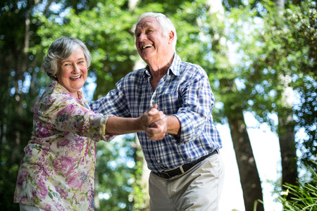 men back: Happy senior woman dancing with husband against trees in back yard