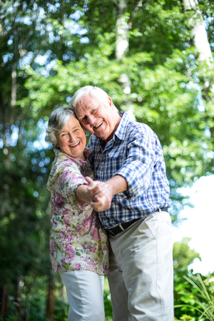 back yard: Portrait of senior couple dancing against trees in back yard