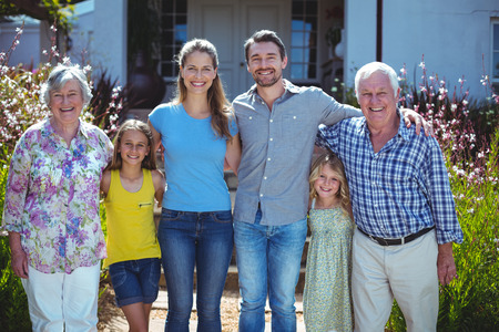 two generation family: Portrait of happy multi-generation family standing against house