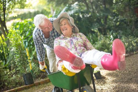 man pushing: Cheerful senior man pushing wife sitting on wheelbarrow in garden