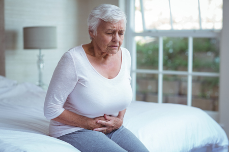 seniors suffering painful illness: Senior woman suffering from stomach pain while sitting on bed