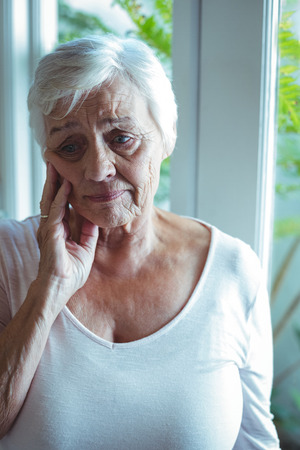 Thoughtful senior woman standing against window at home