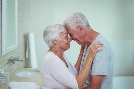 couple bathroom: Romantic senior couple touching nose in bathroom Stock Photo
