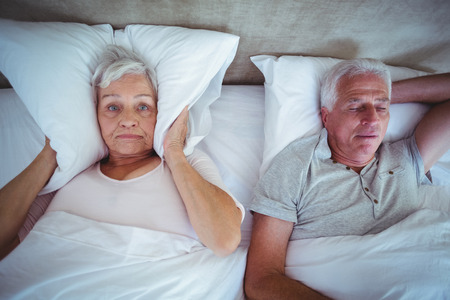 snoring: Annoyed wife blocking ears with pillow while husband snoring on bed