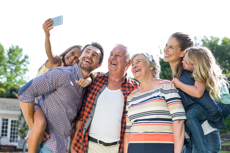 multigeneration: Cheerful girl taking selfie with multi-generation family in back yard