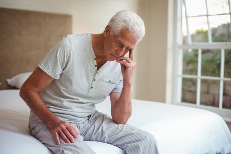 unhappy man: Worried senior man sitting on bed in room