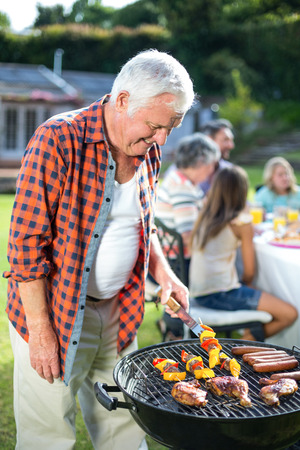 grill tongs sausage: Happy senior man preparing food on barbecue in back yard