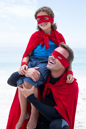 shoulder carrying: Father in superhero costume smiling while carrying son on shoulder at beach Stock Photo