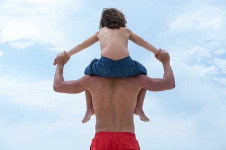 away from it all: Rear view of father holding son hands while carrying him against sky