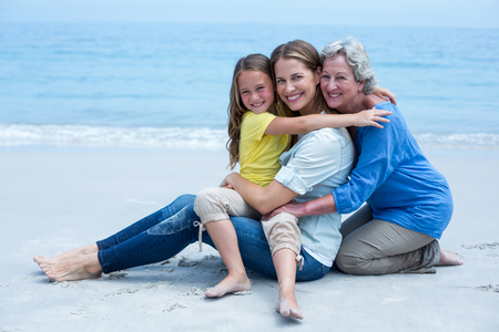 multigeneration: Portrait of cheerful multi-generation family relaxing at sea shore