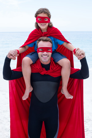 shoulder carrying: Portrait of happy father in superhero costume carrying son on shoulder at beach