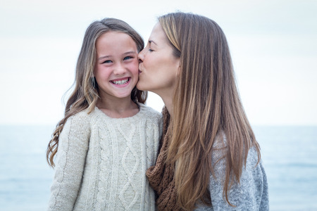 mother kissing daughter: Close-up of mother kissing daughter at beach Stock Photo