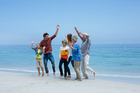 multigeneration: Cheerful multi-generation family dancing at sea shore against blue sky